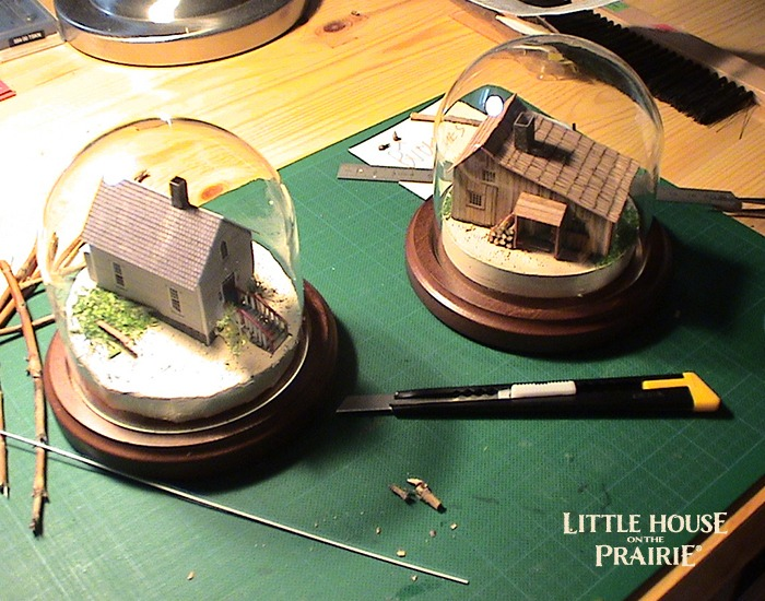 Globes of small models of the school house and Ingalls family home.
