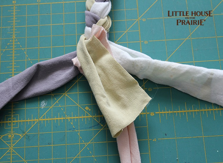 Add a new strip of fabric by overlapping the last two inches and securing it as you braid.
