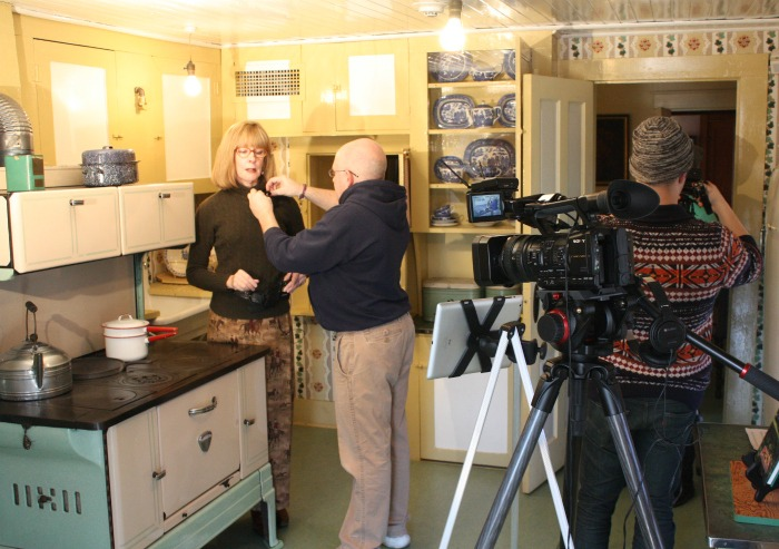 Pamela Smith Hill with Dan Rowland, digital media producer for Missouri State University, prepare to film a lecture in Laura Ingalls Wilder's farmhouse kitchen at Rocky Ridge Farm in Mansfield, Missouri. Also pictured is assistant Drew Mittman.