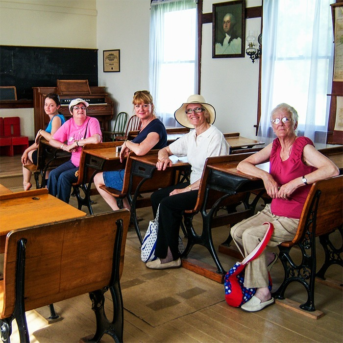 Tour group from the UK in Schoolhouse at Independence, Kansas site.
