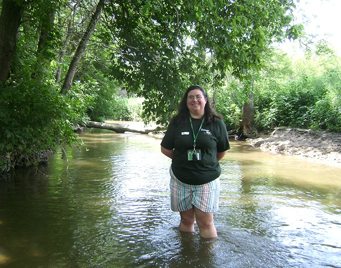 LIWLRA board member Sarah Uthoff wading in Plum Creek