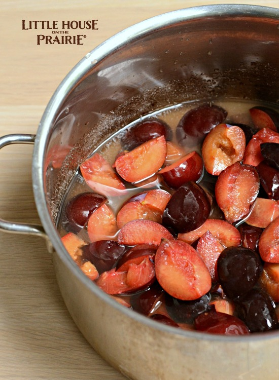 Plums are pitted and halved and ready to boil into preserves.
