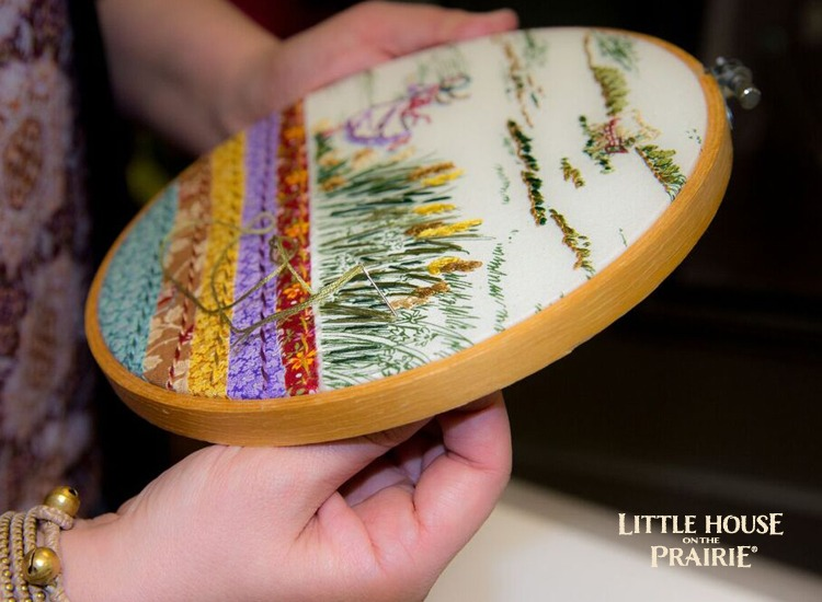 Add the embellishments with embroidery stitches over the fabric's printed design - gorgeous Little House on the Prairie hoop project.