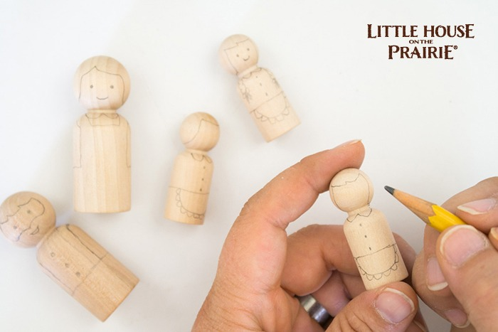 Drawing the simple features onto wooden dolls for homemade toys!